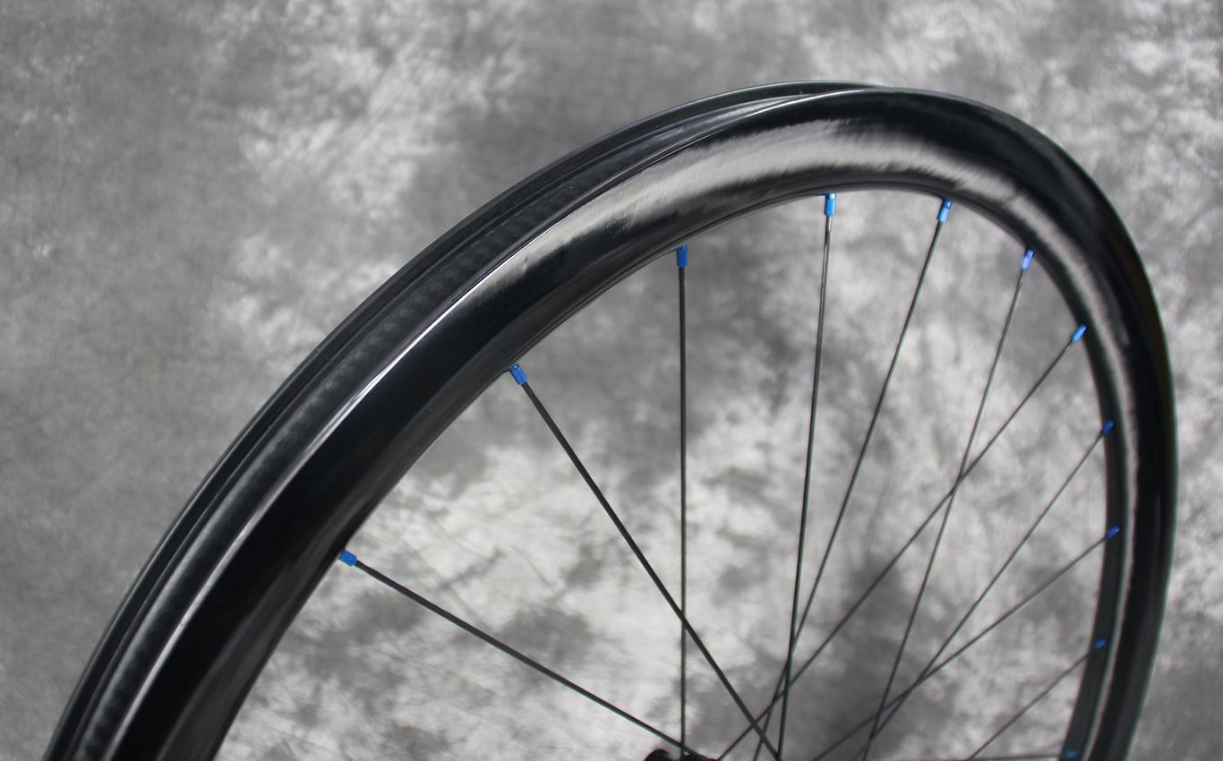 wr38-carbon-rim-paintless-finish-with-blue-spoke-nipples